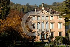 Photo taken with an elegant and beautiful villa located in the hills Hills in the province of Padua in Veneto (Italy). The picture shows the facade of the house of Rose and a part of the front garden with plants with colorful leaves and statues of a sunlit autumn afternoon. Some architectural elements stand out as the glass door of the entrance and a balcony with a triple lancet window. Parrte the top of the building you can see five statues, three central and two lateral.