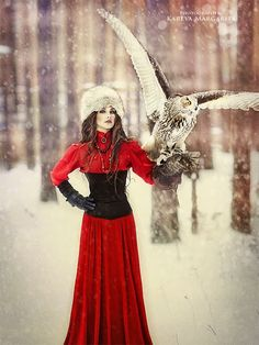 Neo-Victorian Woman in Red with Owl & Fur Hat (From 'Walking in a Winter Wonderland') - For costume tutorials, clothing guide, fashion inspiration photo gallery, calendar of Steampunk events, & more, visit SteampunkFashionGuide.com