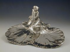 Polished pewter visiting card tray with typical Art Nouveau semi-clad maiden sitting on a rocky outcrop. - Ca. 1906