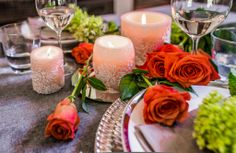 Romantic table setting with ivory & white candles and coral coloured roses.