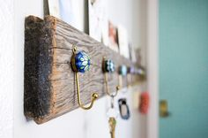 On a piece of scrap wood (the piece used here was an old floorboard) make evenly spaced marks then attach a row of hooks. A groove along the top of the wood provides a place for displaying photos and postcards. Weathered Wood, Old Wood, Barn Wood, Diy Hooks, Wall Hooks, Wooden Key Holder, Diy Rack, Decorative Hooks, Garden In The Woods