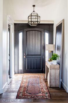entryway with black front door and a kilim rug