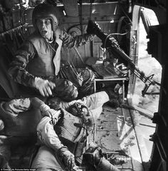 """""""Somebody help: James C. Farley (left) with a jammed machine gun shouts to crew as wounded pilot James E. Magel lies dying beside him"""". (Photo by Larry Burrows/Time"""