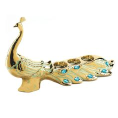 Peacock Jewel Candleholder - This bold and bright peacock has arrived to light up your home! The golden figurine is decorated with worn green touches and sparkling turquoise jewels that will dazzle you and its tail has spaces for three of your favorite tealight candles.