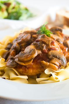 Boneless, skinless chicken thighs and mushrooms simmered in a rich tomato sauce and served over a bed of egg noodles. An easy weeknight version of the classic Italian dish. Recipe includes nutritional information, small-yield, make-ahead, and freezer instructions. From BakingMischief.com