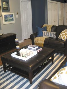 Here you can see the colour scheme come alive with it's fresh white, bight navy blue and a touch of caramelized yellow. Look how the beachy striped rug picks up the heaviness of the dark leather furniture. Open Shelving, Shelves, Round Ottoman, Striped Rug, Leather Furniture, Glass Table, End Tables, Love Seat, Blinds