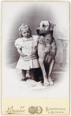 A little tot and her not so little dog and protector. From the e-book, Dressing up with Dogs.