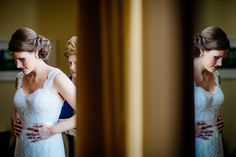 Quiet wedding day moment with reflection as bride's mom helps her get dressed