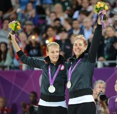 United States silver medalists Jennifer Kessy and April Ross celebrate on the podium with their medals in the women's beach volleyball medal ceremony