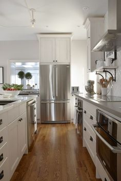 Sarah Richardson Design  Amazing kitchen with gray walls paint color, Ikea kitchen cabinets with Silestone Grey Expo countertops, kitchen island with calcutta marble countertop and subway tiles in herringbone pattern backsplash.
