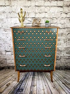 A stunning retro Wrighton chest of drawers made in the 1960s. The dresser is made of teak veneer which is still in a lovely vintage condition, considering its age. The whole piece was treated with wax oil and the drawer fronts received a teal/bronze hexagon print. The original