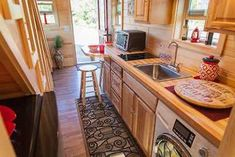 This is the Freedom TM tiny home on wheels. On the outside, you'll notice pine siding, an octagonal window, and a red metal roof. When you go inside you'll find a living room, kitchen a… Tiny Houses For Sale, Tiny House On Wheels, Little Houses, Tiny House Luxury, Tiny House Design, Tiny House Talk, Home Design Floor Plans, Tiny House Listings, Cottage Living