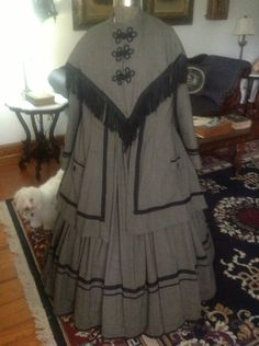 Beautiful 1860s Wool Travelling Suit NOT ORIGINAL.  paletot and dress to match. The paletot has an attached cape at the stand up collar. The black fringe is very narrow as an original would have. (Not silk). It has black frogs   completely lined with polished cotton..( brown). There is wool braid in two sizes to trim and patch faux pockets with black vintage glass buttons. There is a self fabric tab to pull the back into a beautiful shape finished with 2 vintage glass buttons.