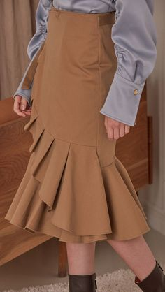 Rosalyn Skirt in Brown. Gently flare out creating ruffle along the right side. Wrap around construction with coordinating attached sash, concealed waistline buttons. Overlapping front structure. Ruffl