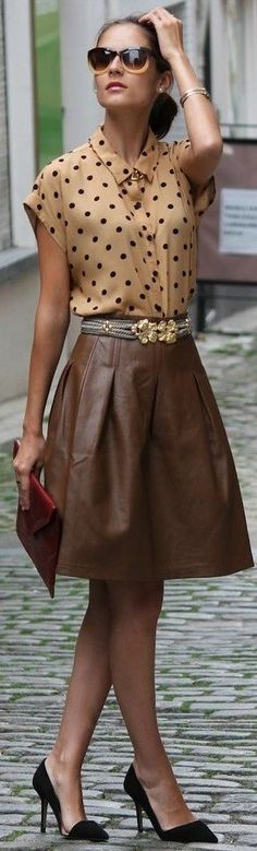 Camel polka dots blouse and leather skirt in combination with black shoes and red handbag.