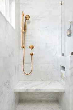 White Marble Tile Bathroom a brass and lucite towel holder lines a glass and marble shower