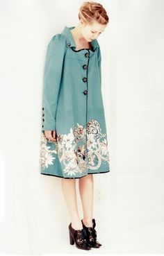 Powder blue coat or coatdress?  It is just darling,  and the shoes complement the black buttons so well.  Lovely!