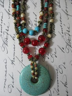 Turquoise, Red Glass, and Earth Tone Owls Statement Necklace. Boho. Bohemian, Bronze Owl Details. Beaded Bib Necklace. Handcrafted, three strand statement necklace featuring natural turquoise, goldstone, mother of pearl, and picture jasper beads. Lots of ruby red Czech glass, with
