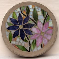 This concrete stepping stone is decorated with a stained glass mosaic featuring two clematis style flowers with mixed colour background. Each circular stone is ( just under ) across and about ( just over inches ) thick. Mosaic Crafts, Mosaic Projects, Stained Glass Projects, Stained Glass Patterns, Mosaic Patterns, Mosaic Flowers, Stained Glass Flowers, Stained Glass Art, Mosaic Stepping Stones