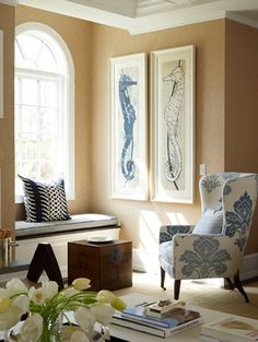 Beautiful corner with lovely seahorse art on a sand-colored wall. Spot of blue repeated in the chair. Great window shape.