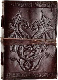 """Hand tooled blank leather journal with embossed double dragons. Border embossing may vary. Sizes vary slightly. Leather, handmade paper. 240 pages, cord closure. 5"""" x 7"""""""