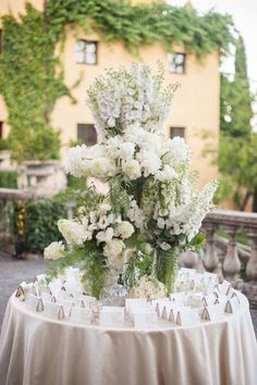 This flower arrangement is over-the-top, but the monochromatic color scheme keeps the table feeling elegant and timeless.   - HarpersBAZAAR.com