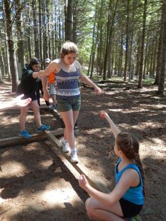 A camper assisting another camper to complete the balance beam challenge! #Leaders #Encouragement #Friendship