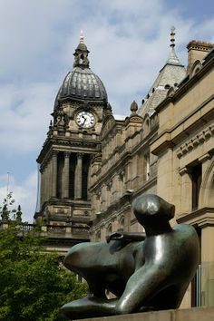 U.K. Henry Moore sculpture outside of Leeds art gallery. Leeds town hall tower in the background.