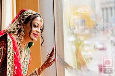 Indian bride watching baraat from hotel window via IndianWeddingSite.com