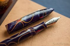 An Edison Nouveau Premiere in an autumn inspired flat lay of fountain pens, notebooks, and ink, with navy blues, browns, and yellows.
