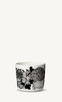 The coffee cup without handle is decorated with a white, black and yellow Siirtolapuutarha pattern. It's made of dishwasher, oven, microwave and freezer proof white stoneware.