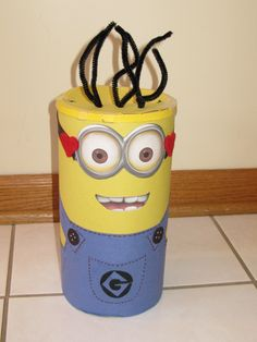 "Minion Valentine Box:  Wrap a large oatmeal container with construction paper and decorate.  I painted the sides of the lid and glued yellow paper on the top.  If I had more time I would have painted the whole lid to keep the paper from lifting up.  Used free clip art to print out minion eyes and mouth.  Google ""printable minion face art"" to get minion eyes and mouth."