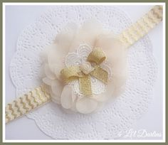 """"""" Willow """"  A sparkly gold chevron headband is the background for this beautiful deep ivory chiffon rosette.  A white embroidered doily is central to the rosette, with a gold bow and ivory satin rose centre.  This headband is professionally hand sewn to your size requirements.  If you would prefer this floral embellishment can be created with a plain ivory satin alice style headband for $1.00 more.   Find Willow Here : http://4lildarlins.com/catalog.php?item=664"""