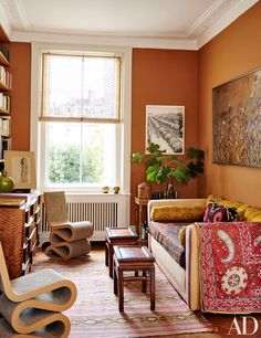 Inside Martina Mondadori Sartogo's Chic, Family-Friendly London Home | An artwork by Christo and Jeanne-Claude hangs next to a library window, while an Anselm Kiefer painting is mounted above a sofa grouped with Frank Gehry chairs and Chinese low tables once owned by Martina's father; both the vintage suzani draped over the sofa arm and the antique kilim were found in Istanbul.