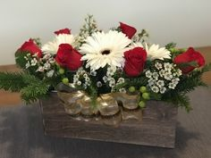 Christmas centerpiece in a wooden box. Red roses and white Gerbera daisies shine with wax flower and fragrant holiday pine greens.