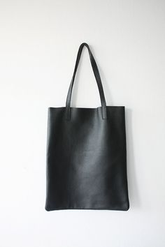This is Anya. Shes a slim, basic black leather tote bag, ideal for everyday.  Lightweight - made from pebbled Italian leather. Handles are reinforced