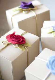 Simple rolled felt flower with 2 leaves at the center of each gift box.