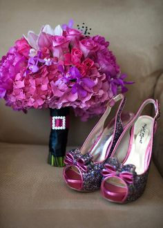 Colorful wedding bridal bouquet using roses and hydrangea with matching sparkling shoes in a palette of pink, red, purple, and black by Pixie's Petals