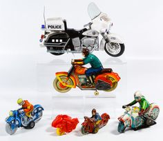 Lot 517: Lithographed Tin Motorcycle Assortment; Six vintage to modern era items including four lithographed tin motorcycles with riders, a battery operated plastic motorcycle and a Thomas toy red plastic motorcycle with sidecar