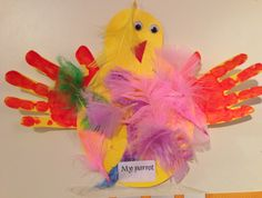 A bird craft using feathers and hand prints for the wings, made by Evan M, 3 years old • Art My Kid Made #kidart #birds #handprint