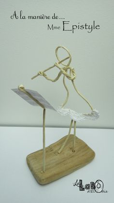 Flutiste sculptée en fil de papier armé, avec détail en crochet blanc.