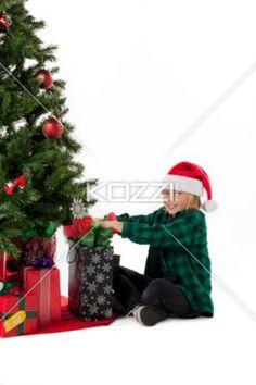 smiling boy opening his christmas gift. - Portrait of a smiling boy opening his christmas gift, Model: Josh Chapman