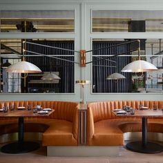 Mid-century-style lamps swivel above burnt orange leather booths inside this restaurant in Chicago, designed by New York-based studio Meyer Davis to occupy an old printing house. #restaurantdesign