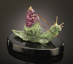 """Ruby-in-Zoisite Carving--""""The Frog King Riding a Snail"""" By Luis Alberto Quispe Aparicio Part of a series of fantasy objects carved from a single piece of rich red, ruby-in-zoisite from Tanzania with gold vermeil antennae and reins, raised on a polished black oval base. Length 6in"""