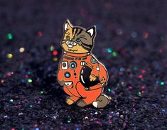 The most adorable space cat pin. His name is Huston, he is wearing his orange…
