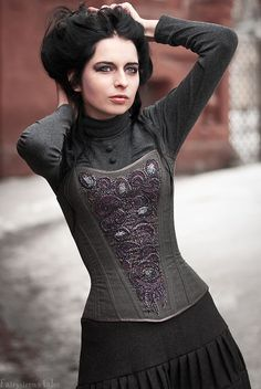DieselSteamGypsy. I love the purple on her corset and her top looks like just a simple turtleneck with cloth covered buttons added.  Awesome! :)