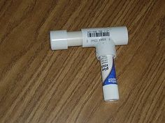 This is an adapted glue stick holder. The person used PVC pipe to hold the glue stick in place and make a handle that the student can grasp onto.