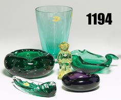 """Estate sale combo: vase, flaring form in green tinted glass, partial paper label, 6.5""""h; with an Erickson tray, feather shape in green and clear glass, paper label, 7.5""""l; with an Erickson bowl, star shape in green glass with radiating bubbles, unmarked, 7.5""""w; with Erickson bowl, small form in purple glass, partial paper label, 4.5""""w; with an Erickson figurine, child in yellow glass, unmarked, 4.5""""h; with an Erickson bowl, thick-walled form in green glass with protruding bubbles, 5.5""""w"""