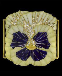 An Art Nouveau diamond set enamel pansy plaque de cou or dog collar centre piece, by René Lalique. The cream coloured pansy with deep blue centre detail and pavé set with graduated circular cut diamonds in gold. Signed LALIQUE