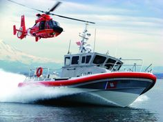 THE COAST GUARD: AMERICA'S OLDEST MARITIME DEFENDERS; A 45 foot patrol boat along with an HH-65 helicopter training off the coast of Alaska.